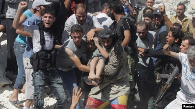 Free Syrian Army fighters and civilians help a wounded boy rescued from under rubble after what activists said was shelling by forces loyal to Syria's President Bashar al-Assad in Aleppo's Bustan al-Qasr district, Aug. 16, 2013.