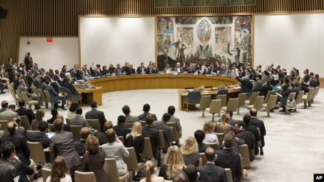 In this photo provided by the United Nations, the United Nations Security Council votes on a resolution that threatens Syria with new sanctions in New York, July 19, 2012.