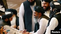 دوحہ میں طالبان وفد کے ارکان مذاکرات کے موقع پر افغان حکومت کے وفد سے مصافحہ کر رہے ہیں۔ 10 دسبمر 2020