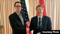 2018年10月10日,美國財政部長努欽和中國人民銀行行長易剛在國際會議期間握手,努欽說雙方討論了重要經濟問題(努欽推特圖片)。