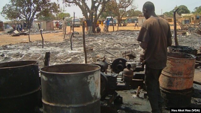 A man looks over what remains of one of the dozens of shops that were gutted by fire in a market in Aweil, South Sudan on Thursday, March 28, 2013. (VOA/Hou Akot Hou)