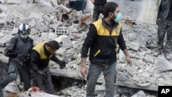FILE - This photo released March 13, 2018, by the Syrian Civil Defense group known as the White Helmets, shows members of the group removing a body after airstrikes and shelling by Syrian government forces, in Ghouta.