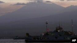Sebuah kapal feri melintasi Selat Bali membawa warga ke pelabuhan Ketapang, Jawa Timur, dari Gilimanuk, sementara di latar belakang Gunung Raung mengeluarkan asap vulkaniknya (12/7).