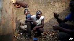 Men take cover in a toilet as heavy gunfire erupts in the Miskin district of Bangui, Central African Republic, Monday Feb. 3, 2014. In what a French soldier on the scene described as the heaviest exchange of fire he'd seen since early December 2013, Musli