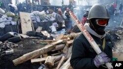 27일 우크라이나 수도 키에프에서 반정부 시위대가 진압 경찰과의 사이에 바리케이드를 설치하고 있다. 우크라이나 법무장관은 비상사태 선포 가능성을 경고했다.