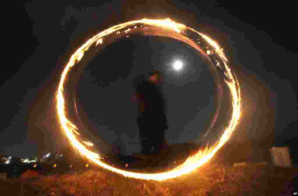 A resident twirls a can with holes filled with burning wood chips and straws to celebrate the first full moon of the Lunar New Year, in Yongin, South Korea.