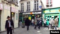 FILE - People walk in the street in the Marais Jewish quarter in Paris.