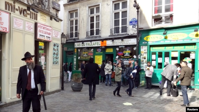 FILE - People walk in the street in the Marais Jewish quarter in Paris.