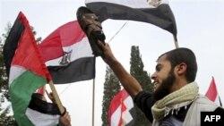 Một người biểu tình Palestine cầm giày và những người khác vẫy cờ Palestine và Ai Cập trong một cuộc biểu tình kêu gọi loại bỏ Tổng thống Ai Cập Hosni Mubarak tại Gaza, 3/2/2011
