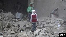 Des enfants marchent dans les ruines à Hamouria, dans la région de la Ghouta, le 22 février 2018.