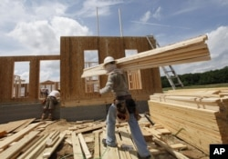 FILE - A construction worker carries a load of wood to a new home as they frame the house in Chester, Virginia, May 16, 2012.