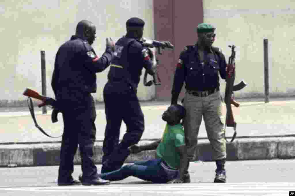 Policemen beat up a protester during a rally against fuel subsidy removal on Ikorodu road in Nigeria's commercial capital Lagos January 3, 2012. Hundreds of demonstrators in Nigeria's commercial capital Lagos shut petrol stations, formed human barriers al