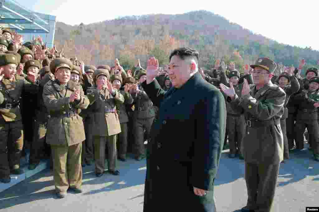 김정은 국무위원장(가운데)이 탄도미사일 시험발사를 실시한 화성포병부대 부대원들을 격려하고 있다.