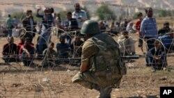 Para pengungsi Suriah menunggu di perbatasan Turki di Suruc (21/9).