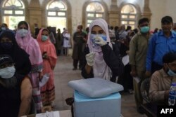 A health worker prepares to inoculate a man with a dose of the Sinopharm Covid-19 coronavirus at a vaccination centre in Karachi on May 26, 2021.