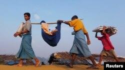 10月24日緬甸羅興亞人在孟加拉國難民營將一名患病親屬抬往難民營醫療中心。