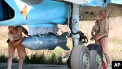 Russian military support crew attach a satellite guided bomb to SU-34 jet fighter at Hmeimim airbase in Syria, Oct. 3, 2015.