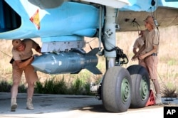 FILE - Russian military support crew attach a satellite guided bomb to SU-34 jet fighter at Hmeimim airbase in Syria, Oct. 3, 2015.