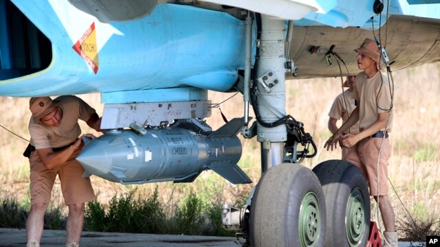 FILE - Russian military support crew attach a satellite-guided bomb to an SU-34 jet fighter at Hmeimim airbase in Syria, Oct.  3, 2015.