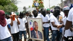 Manm gang 'G9' Jimmy Cherizier yo (alyas Barbecue) kenbe yon foto defun Prezidan Jovenel Moise pandan yon mach pou mande jistis nan Potoprens, Ayiti, 26 Jiye, 2021