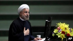 Iranian President Hasan Rouhani speaks during the debate on the proposed Cabinet at the parliament, in Tehran, Iran, said his country will press forward with efforts to ward off military action against Assad regime, Aug. 15, 2013.