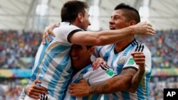 Argentina's Lionel Messi (L-R) celebrates with teammates Angel Di Maria and Marcos Rojo after scoring against Nigeria during their 2014 World Cup Group F soccer match at the Beira Rio stadium in Porto Alegre, June 25, 2014.
