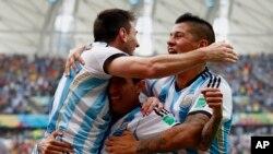 Lionel Messi (kiri) merayakan gol Argentina dengan pencetak gol Angel Di Maria dan Marcos Rojo di São Paulo, Selasa (1/7).