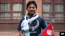 Japanese climber Nobukazu Kuriki poses with a Nepalese flag during a news conference in Kathmandu, Nepal, Aug. 23, 2015.