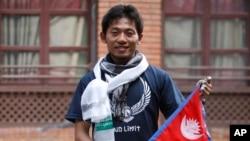 Pendaki Jepang Nobukazu Kuriki berpose dengan bendera Nepal di sela-sela konferensi pers di Kathmandu, Nepal, 23 Agustus 2015.