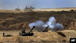 An Israeli tank fires towards Gaza, near the Israel and Gaza border, July 27, 2014.