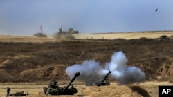 An Israeli tank fires towards Gaza, near the Israel and Gaza border, July 27, 2014.