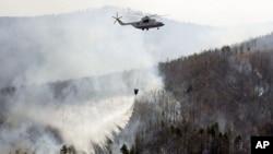 Un hélicoptère russe de secours survole un feu de forêt près de la ville sibérienne de Tchita, à environ 4700 km (3000 miles) à l'est de Moscou, 2 mai 2003.