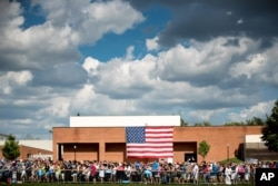 Members of the audience stand in front of a large American flag as Democratic presidential candidate Hillary Clinton, accompanied by Democratic vice presidential candidate, Sen. Tim Kaine, D-Va., speaks at at rally at Fort Hayes Metropolitan Education Center in Columbus, Ohio, July 31, 2016.