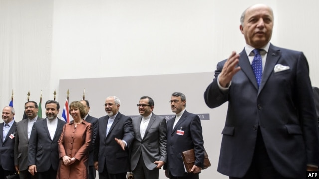 French Foreign Minister Laurent Fabius (R) gestures as EU foreign policy chief Catherine Ashton (4thL) pose with Iranian Foreign Minister Mohammad Javad Zarif (5thL) next to the Iranian delegation after a statement on Nov. 24, 2013 in Geneva.