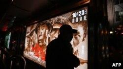 """在北京街頭一個公交車站一名男子走過顯示中國志願軍參加朝鮮戰爭的電影""""金剛川""""的廣告箱。(2020年10月22日)"""