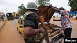 A gendarme checks a driver's car at a checkpoint in the PK4 district of Bangui, Feb. 27, 2014.