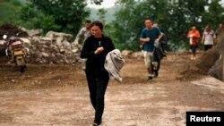 Warga berlari melewati bukit yang beresiko mengalami longsor setelah gempa bumi melanda Ludian di Zhaotong, Yunnan, 3 Agustus 2014.