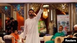 FILE - Aamir Liaquat Hussain gestures during a live show in Karachi, Pakistan, July 26, 2013.