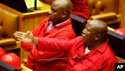 File - South African Economic Freedom Fighters leader Julius Malema (Right) gestures during a session in Parliament, in Cape Town, South Africa, March 2015.