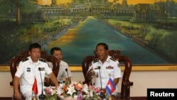 Tea Vinh, commander of the Royal Cambodian Navy (R), welcomes Yu Manjiang, commanding officer of the Chinese fleet visiting Cambodia, in Phnom Penh, Feb. 24, 2016.