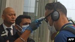 Seorang petugas memeriksa suhu tubuh atlet kriket Faf du Plessis (kanan) setibanya di Kolkata, India, 16 Maret 2020. Afrika Selatan mendeklarasikan wabah virus corona (COVID-19) sebagai bencana keamanan nasional, Minggu (15/3).