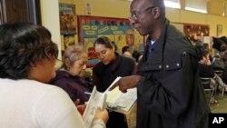 投票站工作者菲利普在洛杉矶北好莱坞图书馆帮助选民们正确投票(2016年10月30日)