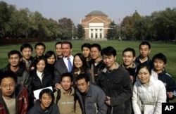 FILE - Former California Gov. Arnold Schwarzenegger poses for a group photo with students during a visit to Tsinghua University in Beijing Wednesday Nov. 16, 2005.