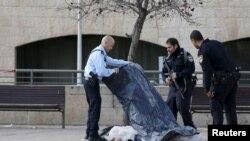 Polisi Israel berdiri di dekat jenazah stina yang ditembak mati setelag berupaya menusuk seorang polisi di dekat Kota Tua Yerusalem (26/12).