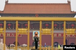 A paramilitary policeman stands guard before a giant portrait of late Chinese Chairman Mao Zedong at the Tiananmen gate, a day before the 19th National Congress of the Communist Party of China begins, in Beijing, China, October 17, 2017.