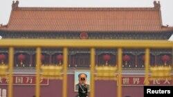 Một cảnh sát đứng canh trước chân dung vĩ đại của cố Chủ tịch Mao Trạch Đông tại Thiên An Môn, một ngày trước Ðại hội Ðảng Cộng sản Trung Quốc lần thứ 19 khai mạc ở Bắc Kinh (ngày 17/10/2017).