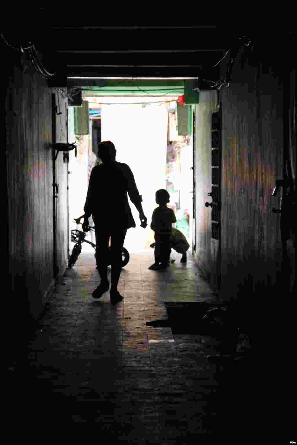A resident and children walk through ​a dark corridor inside the White Building on Friday, September 5, 2014. (Nov Povleakhena/VOA Khmer)