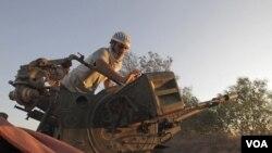 Seorang tentara pemberontak mempersiapkan senjata anti pesawat di dekat Zlitan, Libya barat (1/8).