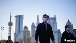 戴着口罩的行人行走在上海陆家嘴金融区的街道上。(2020年3月19日)