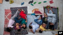 An Indian family sleeps on the roof of a house to beat the heat in New Delhi, India, May 29, 2015. (AP Photo/Tsering Topgyal)